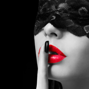 Hush. Sexy woman with finger on her red lips. Lace mask